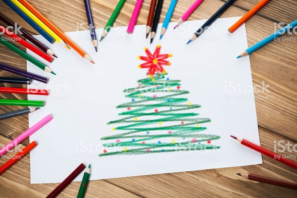 Children's drawings on white paper with colorful pencils on the wooden table